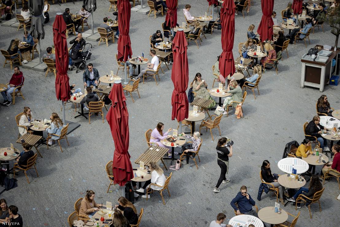 Vendégek egy utrechti kávéház teraszán 2021. április 28-án, amikor a koronavírus-járvány miatt bevezetett korlátozások enyhítéseként újra kinyithattak a vendéglátóhelyek teraszai Hollandiában