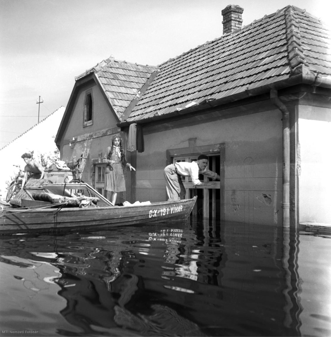 Csónakkal segítik a mentést a vízben álló házakból a júliusi árvíz idején Győr-Révfalu községben 1954. július 25-én.