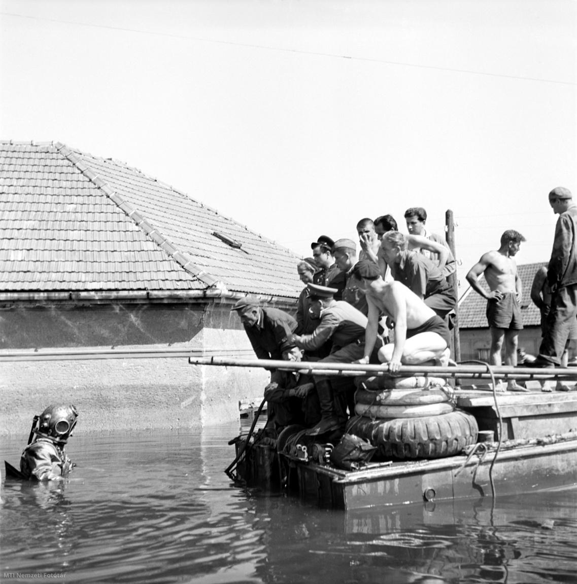A szovjet hadsereg kétéltű járművével szovjet és magyar katonák közösen búvár segítségével vontatják ki a gépkocsikat a három és fél méteres víz alól Győrben, az 1954 júliusi árvíz idején.