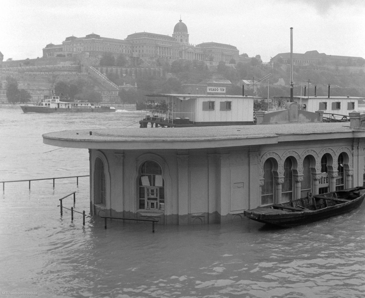 A megáradt Duna folyó által elöntött Vigadó téri hajóállomás épülete a Pesti alsó rakparton 1965. június 10-én. A háttérben a budai Várpalota. A 113 napig tartó dunai árvíz 390 km hosszan magasabb szinten tetőzött minden korábbi, jégmentes árvíznél, és tartósabban tette próbára a védőműveket. A több mint három hónapig tartó áradás hat hullámban vonult le a Dunán. A folyamatos esőzések miatt néhány hét alatt másfélszer több csapadék hullott le, mint más években. Több ezer épület dőlt romba és rongálódott meg súlyosan.