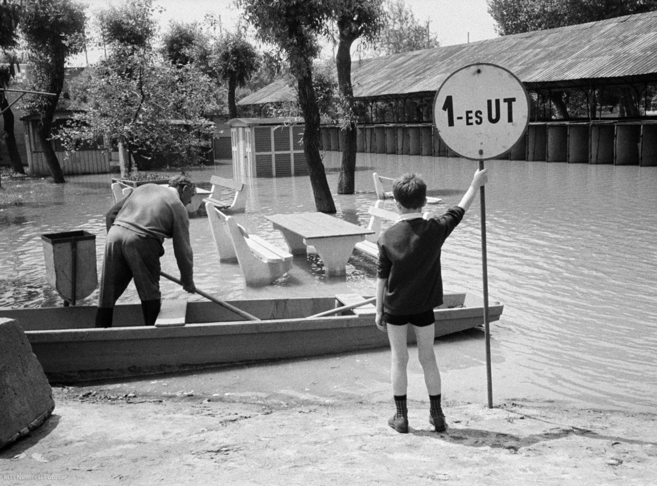 Csónakkal közlekednek a szegedi strandfürdő területén 1965. június 14-én, miután az utóbbi héten naponta 20-25 centimétert áradt a Tisza folyó. A vízszint meghaladja a 600 centiméteres magasságot. A strand alig volt még nyitva és máris víz alá került, ezért be kellett zárni. A padok és asztalok alig látszanak ki a vízből, amely elérte a kabinokat és a víkendházakat is.