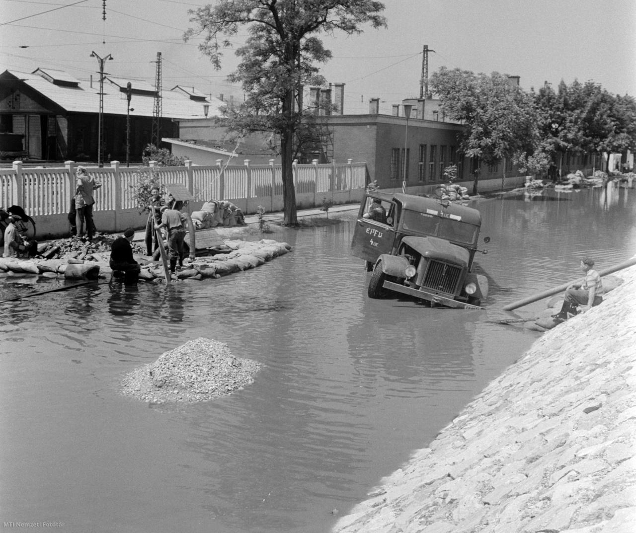Vízzel elöntött utca és elakadt teherautó a vasútállomásnál Komárom és Szőny között a Duna folyó áradása miatt 1965. június 16-án. Ezen a szakaszon a magas vízállás miatt a folyó felőli vágányon homokzsákok zárják el mintegy 400 méteres szakaszon a vizet. A Magyar Államvasutak (MÁV) több mint 3 ezer emberrel védi a vasútvonalat és a komáromi pályaudvart hogy továbbra is közlekedhessenek ezen a szakaszon a hazai és a nemzetközi vonatok. A személyi pályaudvar köré nyúlgátat vontak, a teherpályaudvaron mintegy 800 méteres szakaszon pedig szintén teljes erővel védekeznek.