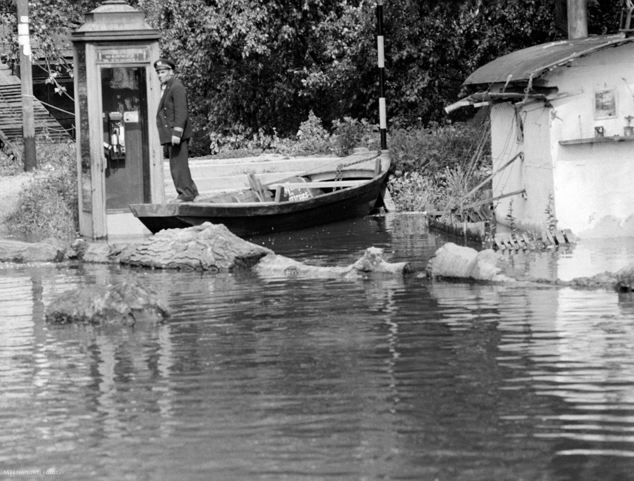 Egy matróz csónakban áll a megáradt Duna folyó mellett egy népszigeti telefonfülkénél 1965. június 17-én. Az árvízi mentésben több a feladatuk a vízirendészeti szerveknek. A kiürített házak a könnyű zsákmány reményében vonzzák a bűnözőket, ezért a Budapesti Vízirendőrőrs teljes létszáma készenlétben van, hajókkal éjjel-nappal járják az elöntött területeket, hogy megakadályozzák a bűncselekményeket, fosztogatásokat. A járőrök irányítják az önkéntes rendőröket, figyelik a gátakat, segítenek a mentésben is, az elsődleges feladatuk, a közbiztonság megőrzése mellett.