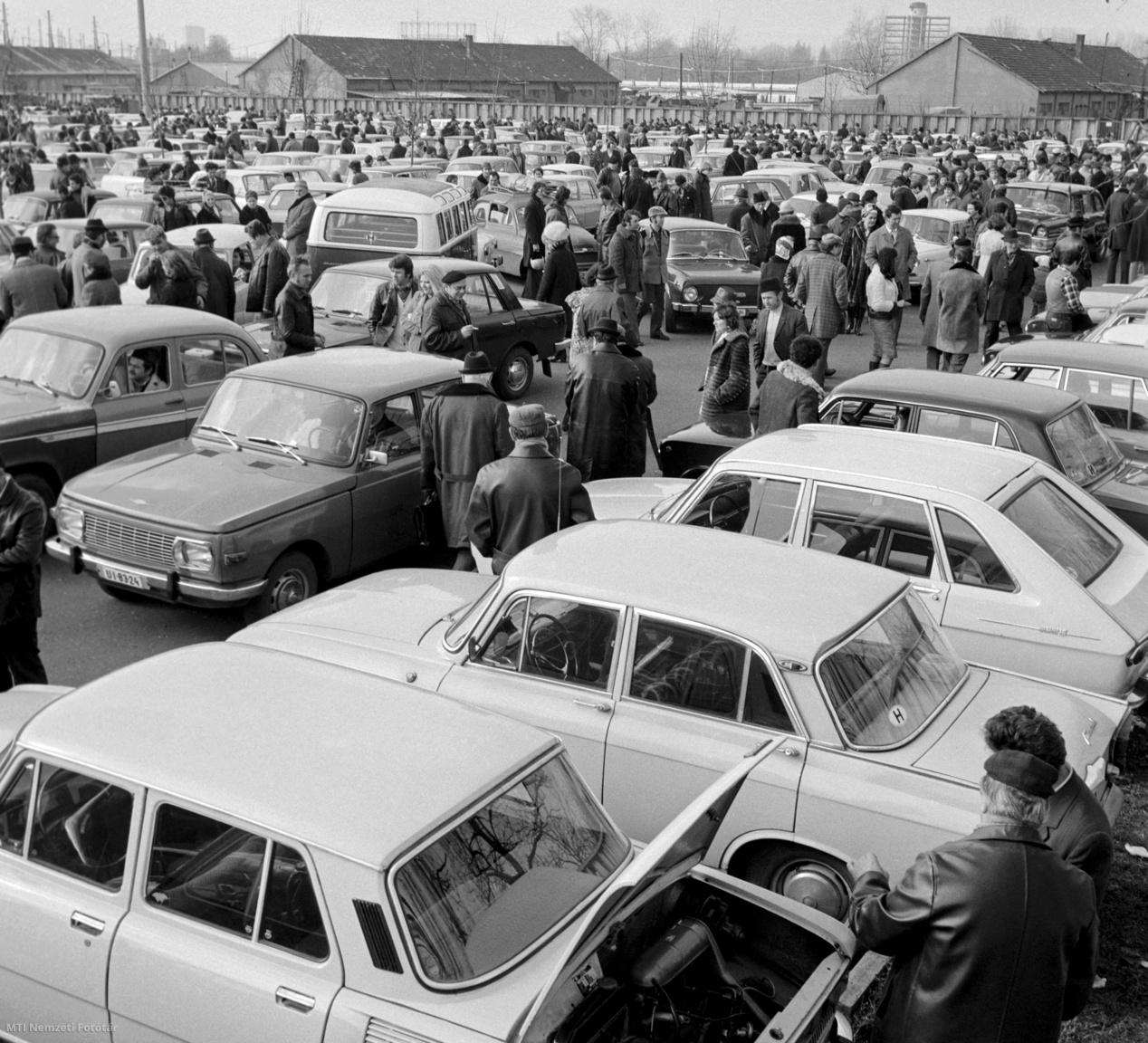 Eladók és vásárlók az angyalföldi használtautó-piacon a Röppentyű utcában 1977. április 17-én. Az előtérben egy Skoda S100-as motorterét mutatja a vevőnek a gépkocsi tulajdonosa.