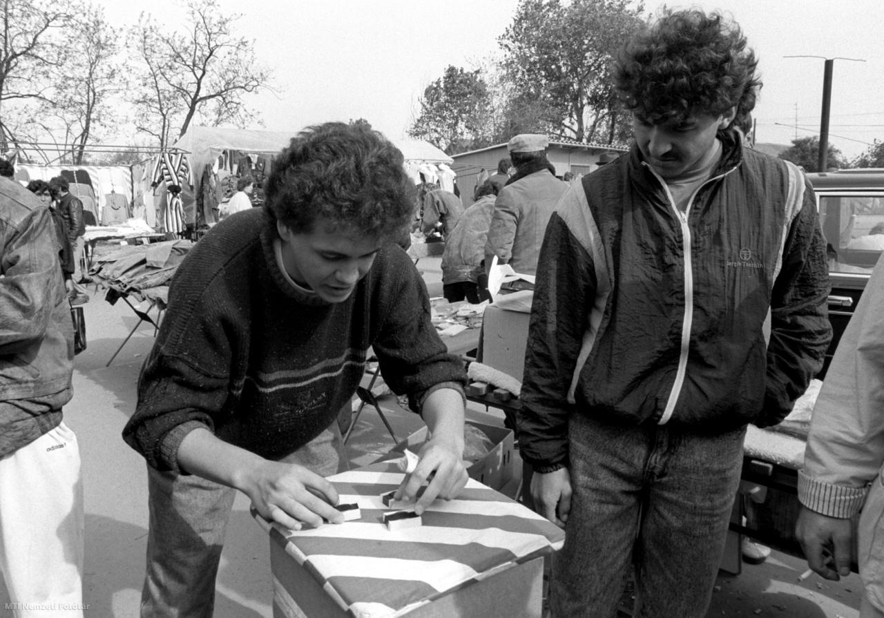 Hazárdjátékos a szegedi Cserepes sori piacon 1990. április 30-án. A Balti-tengertől az Adriáig minden ország képviselteti magát Szegeden a Cserepes soron amely egyesek szerint egyike az ország legnagyobb legszínesebb nemzetközi piacainak. Az árusok és vásárlók forgatagában megtalálható a kispénzű turista és a profi valutaüzér a létminimumon élő nyugdíjas és a hazárdjátékos. Az áruválaszték az élelmiszertől a műszaki cikkekig terjed.