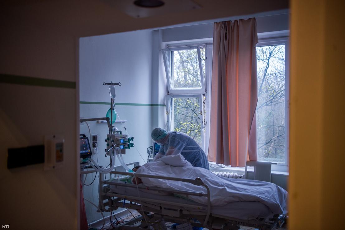 Ápoló egy koronavírussal fertõzött beteget lát el egy kórházban kialakított izolációs teremben 2020. március 25-én