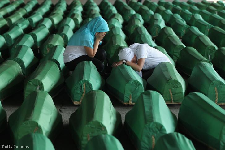 Két muzulmán nő siratja hozzátartozóit az 1995-ös srebrenicai mészárlás 613 exhumált áldozatának 2011-es temetésén