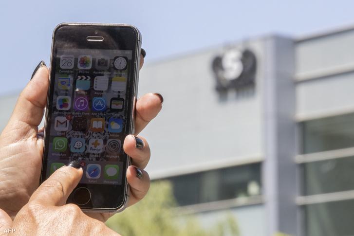 Egy izraeli nő iPhone-ját használja az izraeli NSO Groupnak otthont adó épület előtt
