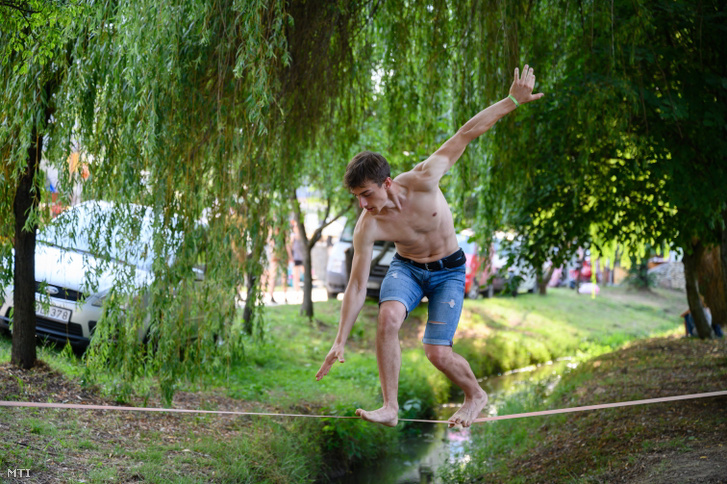 Egy résztvevő kötélen egyensúlyozik (slackline) a 30. Művészetek Völgye fesztiválon Kapolcson a megnyitó napján 2021. július 23-án