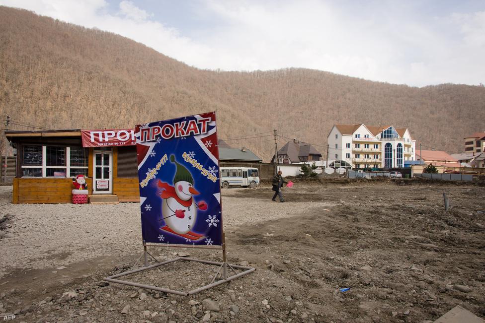 """Hóembert ábrázoló plakát a síversenyek teljesen hómentes helyszínén. A kép február 11-én, egy évvel az olimpiai versenyek előtt készült.                         Annál nagyobb gondot jelenthet a szabadtéri versenyszámoknál. Bár a szubtrópusi klíma csak a városra jellemző, a környező, közel háromezer méteres hegyekben előfordul a hó. """"Szocsi 2014: Garantáltan lesz hó"""" - hangzik az olimpia egyik szlogenje, de egy évvel az olimpia előtt ezt semmi sem igazolta. Idén Február 6-án például alig volt hó, az alacsonyabban fekvő sípályákon 0 fokot mértek, és szakadt az eső. Az egyetlen magasan lévő pályát pedig lavinaveszély miatt lezárták."""