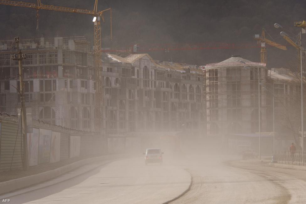 Az építkezések porfelhőjébe borított utca Krasznaja Poljanában, a 2014-es téli olimpia síversenyeinek helyszínén. Kevesebb mint egy év múlva, 2014. február 7-én kezdődik a téli olimpia Szocsiban. Vlagyimir Putyin, Oroszország régi-új elnöke személyes ügyének tekinti az olimpiát, amitől részben az Oroszországról a nyugati világban kialakult kép megváltozását is reméli. Legalábbis erről győzködte Putyin sajtótitkára, Dmitrij Peskov Kathy Lallyt, a Washington Post újságíróját. Lally február második hetében járt Szocsiban a Kreml sajtótúráján, élményeiről riportsorozatban számolt be.