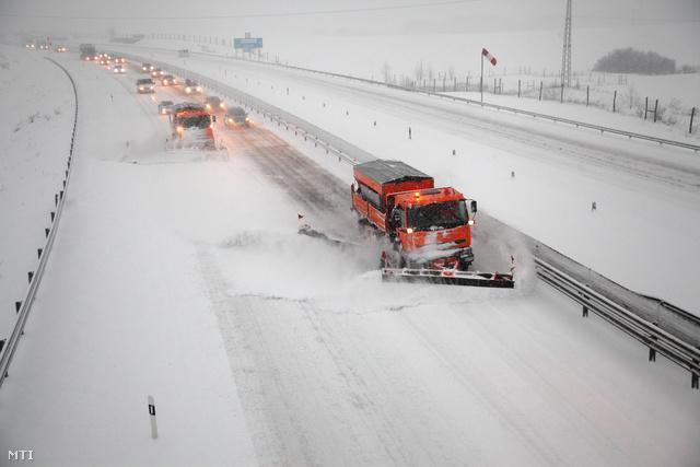 Hókotrók haladnak a feltorlódott autók előtt az M7-es autópályán Nagykanizsa közelében 2013. február 23-án. A térségben reggelre közel 20 cm hó hullott.