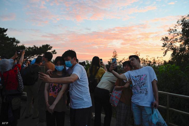Emberek szelfiznek naplementekor Pekingben 2021. július 30-án