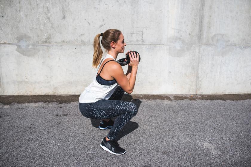 A kettlebell-lel való edzés akkor tesz jót, ha a gyakorlatokat szabályosan végzed. A guggolásokat egyenes háttal hajtsd véghez. Fogd meg mindkét kezedbe a súlyzót, majd végezz széles guggolásokat. Arra figyelj, hogy a térded ne menjen a boka elé.