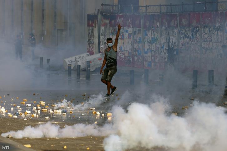 Felelősségre vonást követelő kormányellenes tüntető a győzelem V-jelét mutatja a bejrúti parlament épülete közelében 2021. augusztus 4-én, a város kikötőjében bekövetkezett robbanás első évfordulóján