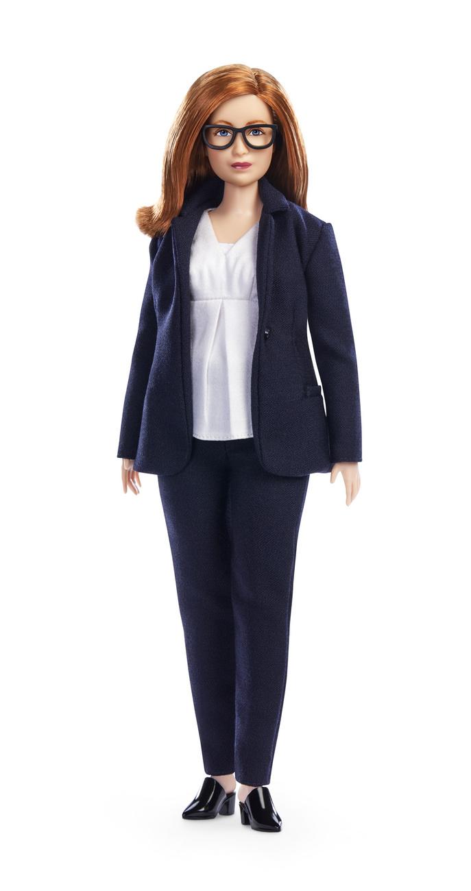 Sarah Gilbert, az Oxfordi Egyetem 59 éves professzora tengerészkék nadrágkosztümöt, fehér blúzt és nagy, fekete keretes szemüveget visel