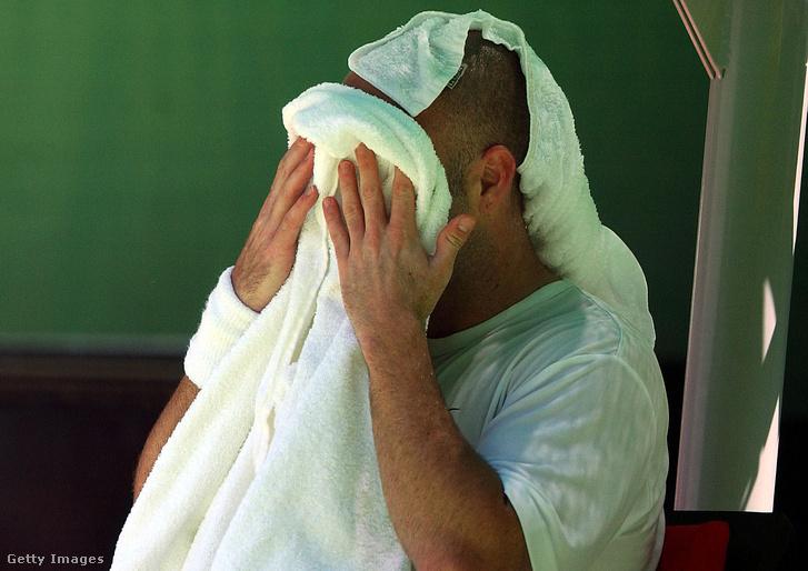 Egy férfi törülközővel törli az arcát