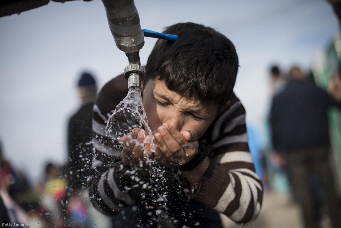 Egy kisfiú vizet iszik egy kútból Görögországban 2016. március 3-án
