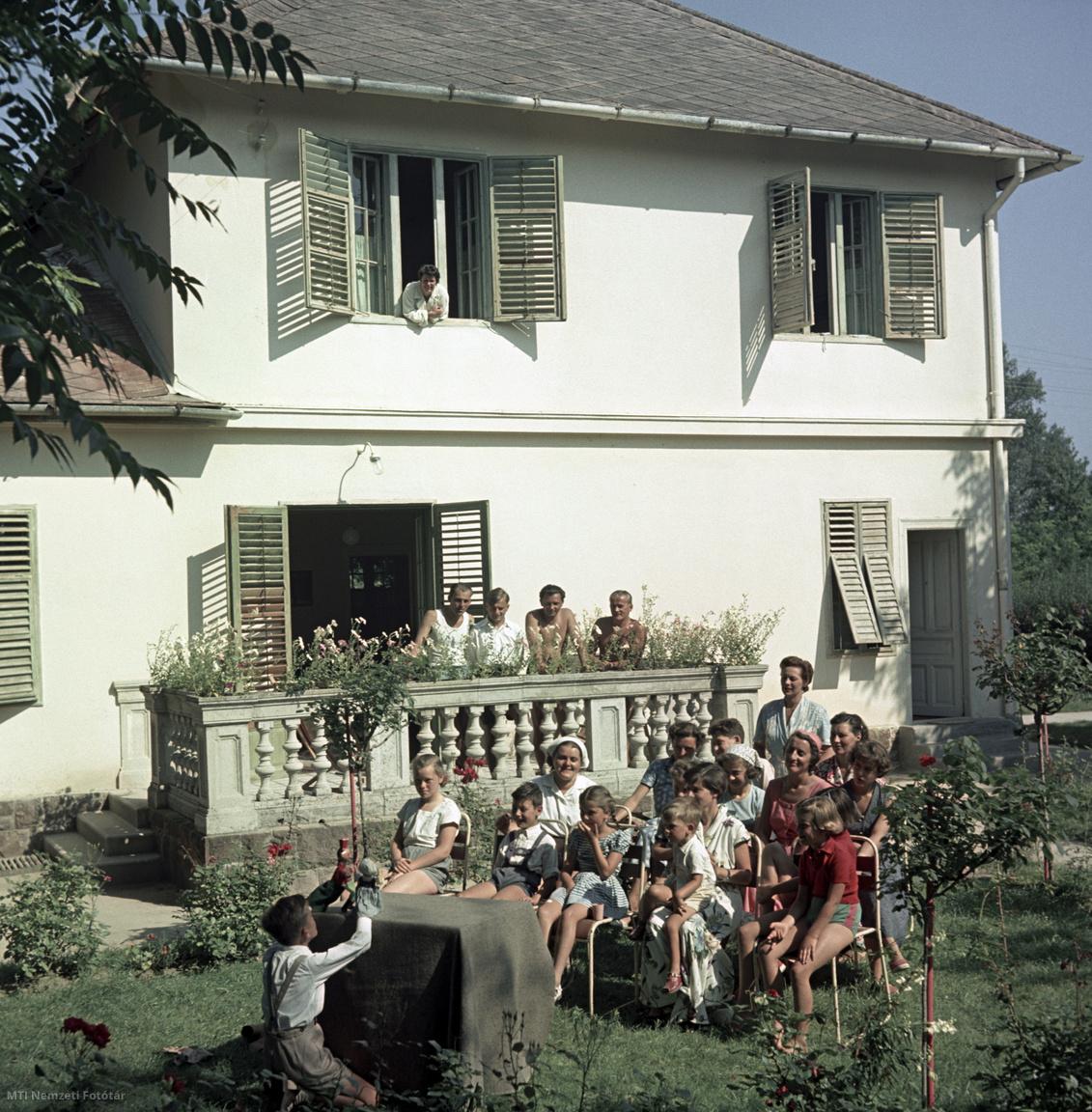 Balatonföldvár, 1957 nyara.  Üdülő gyerekek és felnőttek egy kisfiú bábelőadását nézik egy Balaton-parti üdülő kertjében. A felvétel készítésének pontos dátuma ismeretlen