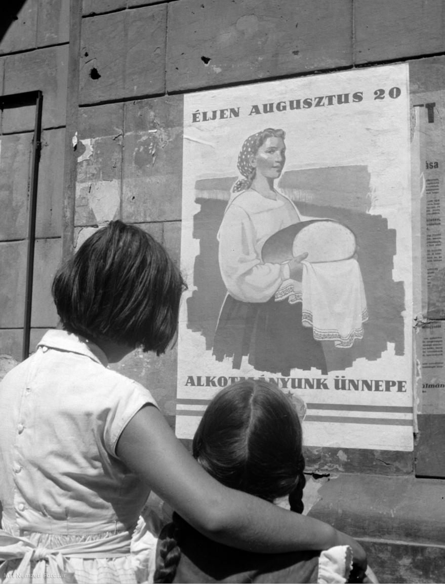 Az Alkotmány ünnepét hirdető plakátot néz egy anya kislányával Budapesten 1957-ben
