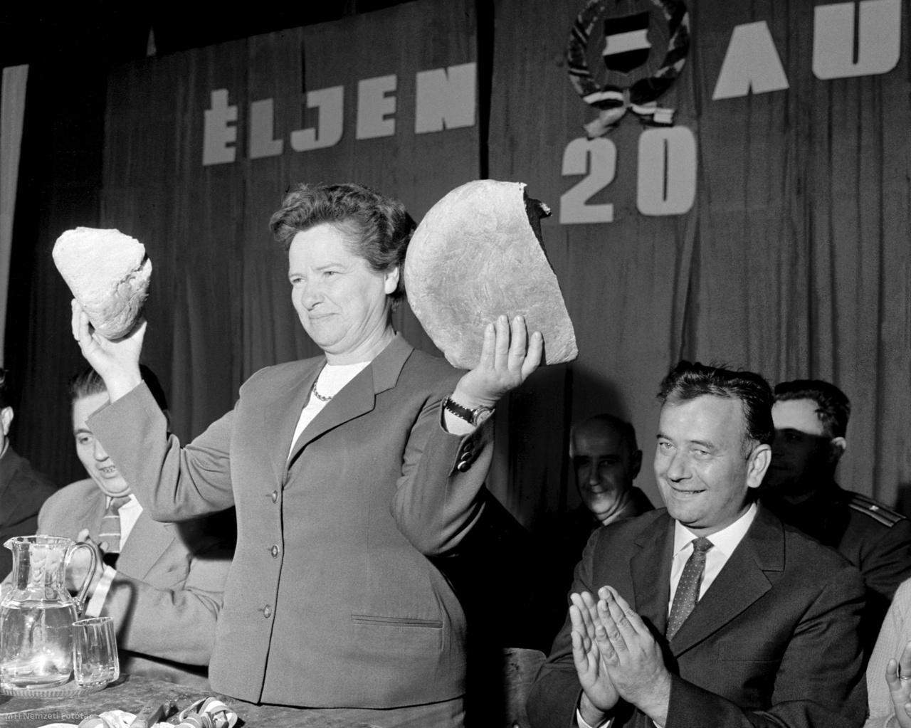 1964. augusztus 20. Juhász Lajosné, a Főváros XV. kerületi Tanács Végrehajtó Bizottság elnökhelyettese felmutatja a megszegett, a Béke Termelőszövetkezet tagjai által adományozott idei első kenyeret az új kenyér ünnepén, az Alkotmány 15. évfordulóján a Czabán Samu téren rendezett ünnepségen