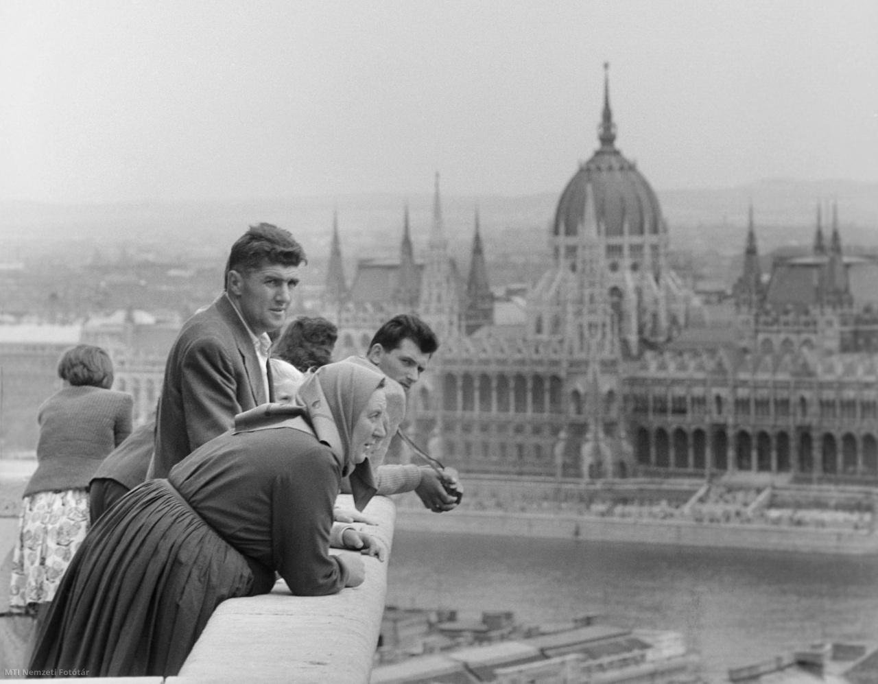 Ünneplők nézik a város panorámáját az Alkotmány 15. évfordulójának ünnepén a Halászbástyán 1964-ben. Jobbra az Országház