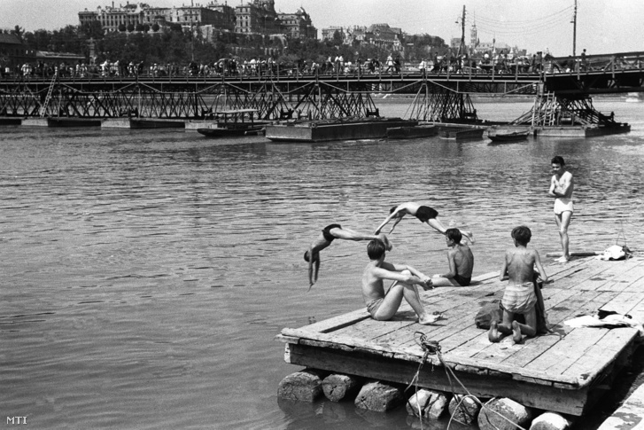 1946, Budapest - Fiatalok fürdőznek az augusztusi kánikulában a Duna-parton. Háttérben a háborúra emlékeztetõ Petõfi pontonhíd látható melyet a népnyelv Böske hídnak nevezett tekintettel arra hogy a lerombolt Erzsébet hidat volt hivatott helyettesíteni.