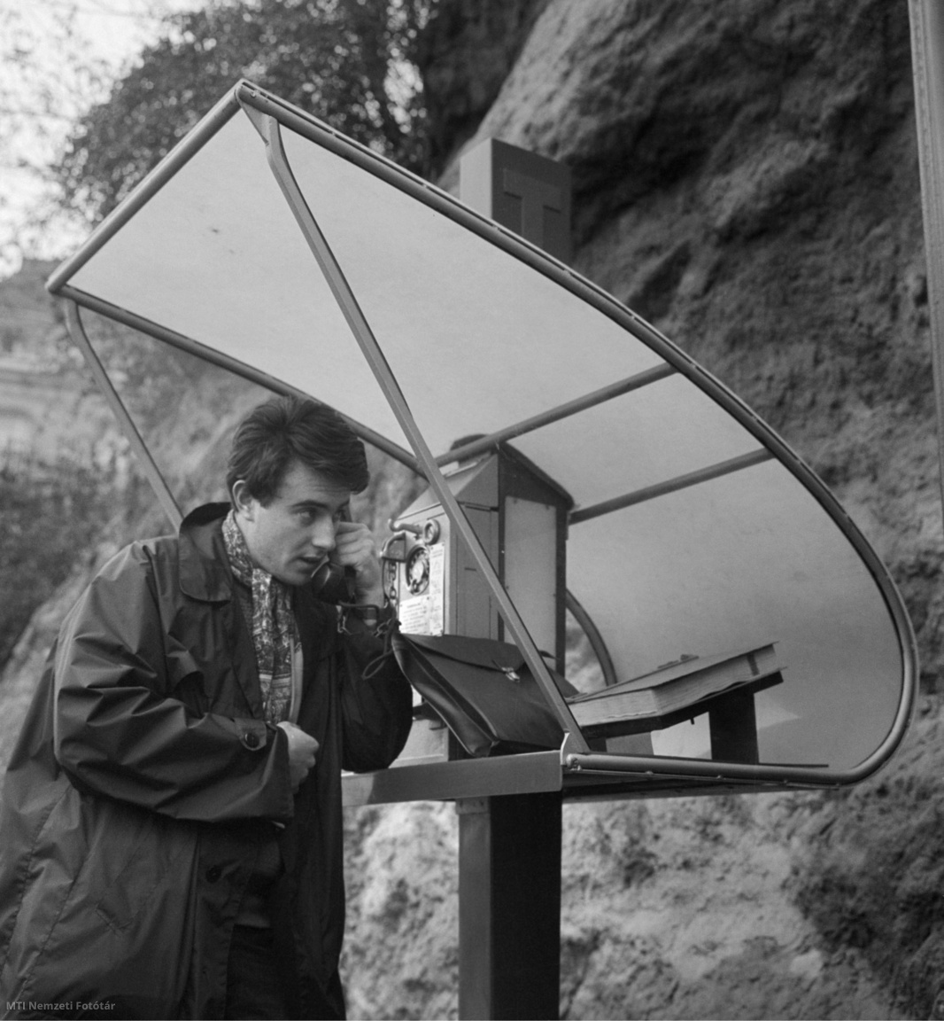 Egy férfi a Magyar Posta által felállított öt új, különböző formájú és színű távbeszélő állomás egyikénél telefonál a Gellért térnél, a Gellért-hegy oldalánál 1962. november 2-án. Az új állomások a Posta által korábban kiírt pályázatra beérkezett tervek prototípusai. Ezek közül egy viszonylag hosszabb üzemeltetés után döntik majd el véglegesen, hogy melyekkel cserélik fel az elavult állomásokat, fülkéket