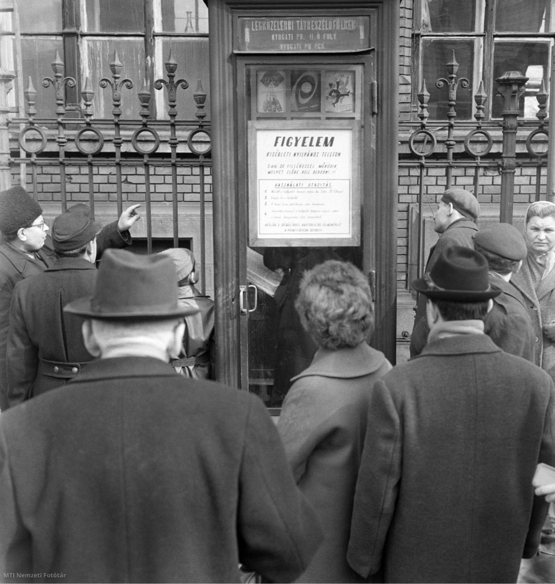 Járókelők nézik a Nyugati pályaudvarnál felszerelt kísérleti telefonfülkét 1964 májusában. Ehhez a típushoz nem kell telefonérme, hanem három darab húszfilléres bedobásával működik