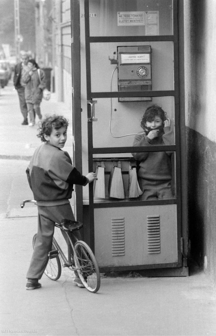 Budapest, 1989. március 9. Biciklis kisfiú vár egy utcai telefonfülkéből telefonáló kislányra a IX. kerületben