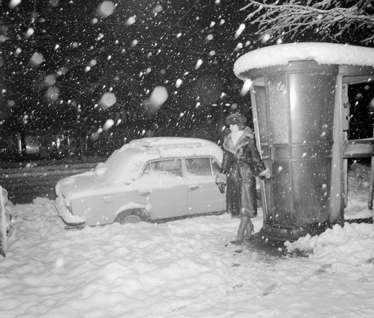Jellegzetes,gombatetejű műanyag telefonfülkéből lép ki egy járókelő a sűrű havazásban 1980. december elsején. Mellette egy Lada személygépkocsi