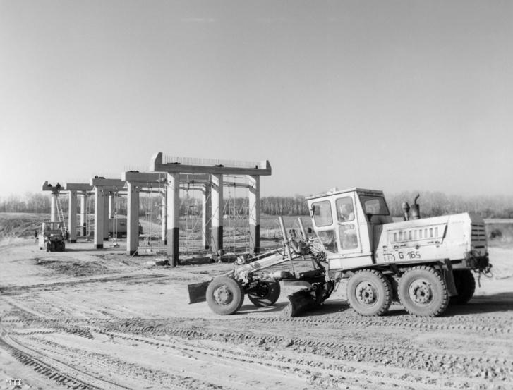 A Közúti Építő Vállalat munkagépei tereprendezést végeznek az épülő közúti felüljáró tartóoszlopai körül 1989. november 17-én