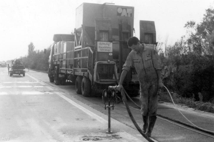 Egy munkás javítja az M7-es autópálya megsüllyedt beton úttestét 1993. október 14-én. Az eljárásnak az a lényege, hogy a megsüllyedt betontáblákat megemelik, szintbe helyezik, alátömítik, majd stabilizálják a talajt