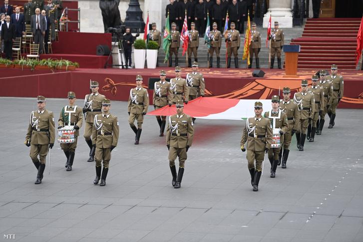 A nemzeti lobogót viszik a díszőrség tagjai a Parlament előtti Kossuth téren tartott Szent István-napi ünnepségen 2021. augusztus 20-án.