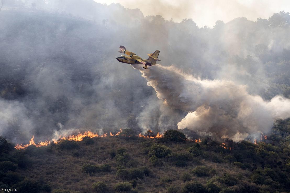 Repülőgépről ledobott tűzgátló anyaggal próbálják megfékezni a lángokat a Tivoli környékén pusztító erdőtűz helyszínén 2021. augusztus 12-én