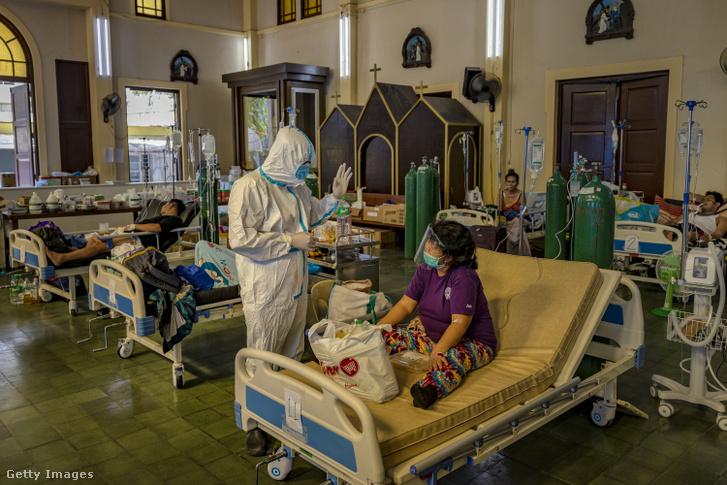 Egy orvos koronavírussal fertőzött beteget lát el egy templomból átalakított kórházban Manilában, a Fülöp-szigeteken 2021. augusztus 25-én