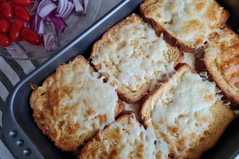 Rakott bundás kenyér sajttal és sonkával rétegezve: a kiadós finomság sütőben sül