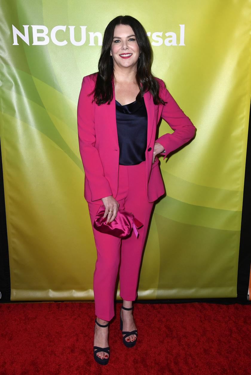 Nőies, modern és sikkes ebben a pink nadrágban és blézerben, melyet fekete szaténfelsővel és fekete cipővel egészített ki. A szett remekül passzol hajához és bőréhez, valamint kiemeli karcsú alakját.
