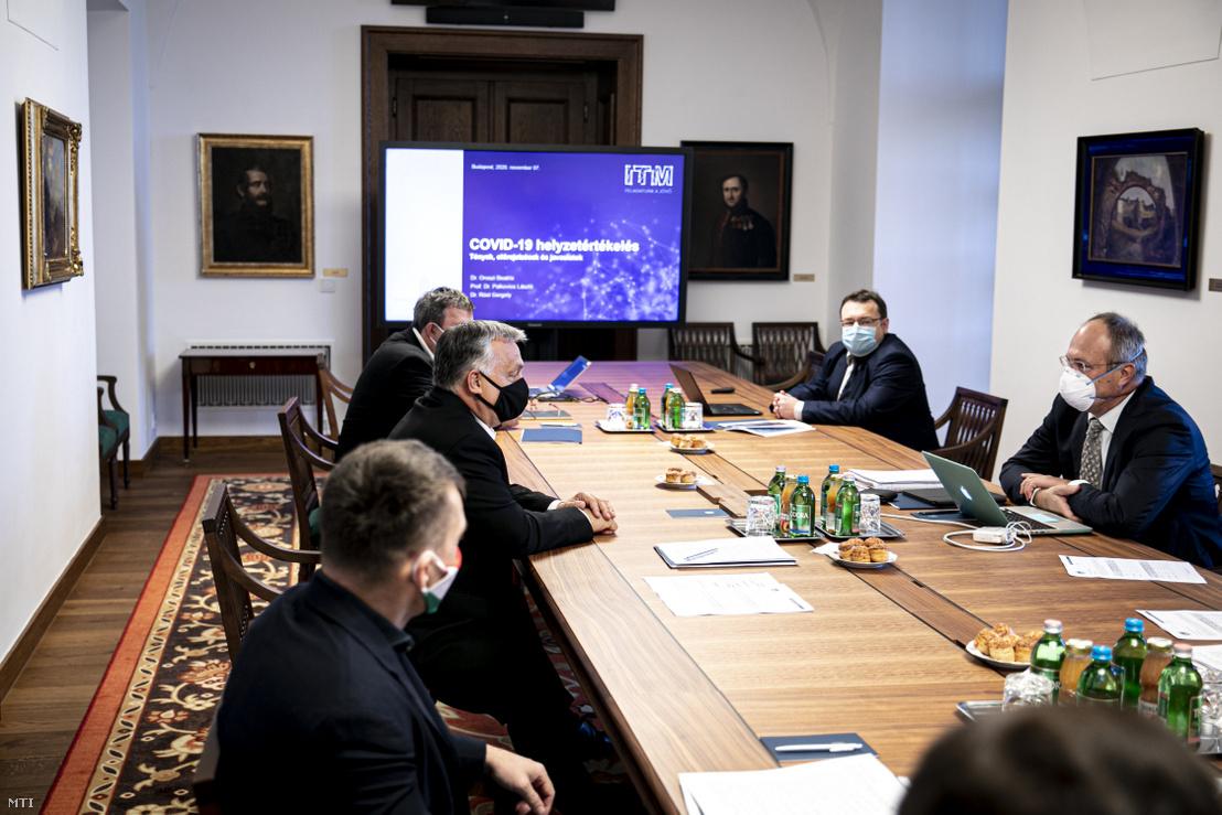 Orbán Viktor miniszterelnök (b3) tudományos szakemberekkel tanácskozik a Karmelita kolostorban 2020. november 7-én. Mellette Gulyás Gergely, a Miniszterelnökséget vezető miniszter (b), Rogán Antal, a Miniszterelnöki Kabinetirodát vezető miniszter (b2), Palkovics László innovációs és technológiai miniszter (b4), szemben Merkely Béla, a Semmelweis Egyetem rektora (j), Szócska Miklós, a Semmelweis Egyetem egészségügyi közszolgálati karának dékánja (j2) és Röst Gergely, a Szegedi Tudományegyetem járványtannal foglalkozó matematikusa (j3)