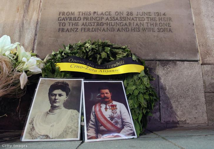 Ferenc Ferdinánd osztrák főherceg és felesége, Zsófia hercegnő arcképe koszorúval a merénylet helyszínét jelző emléktábla alatt