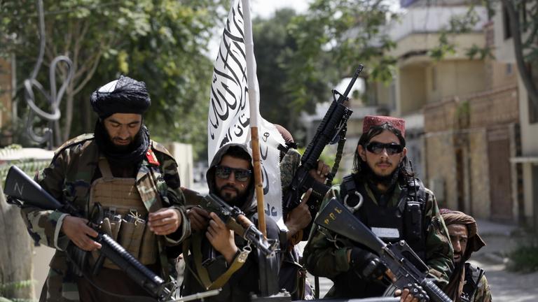Los talibanes con una metralleta detrás, el locutor garantiza la seguridad