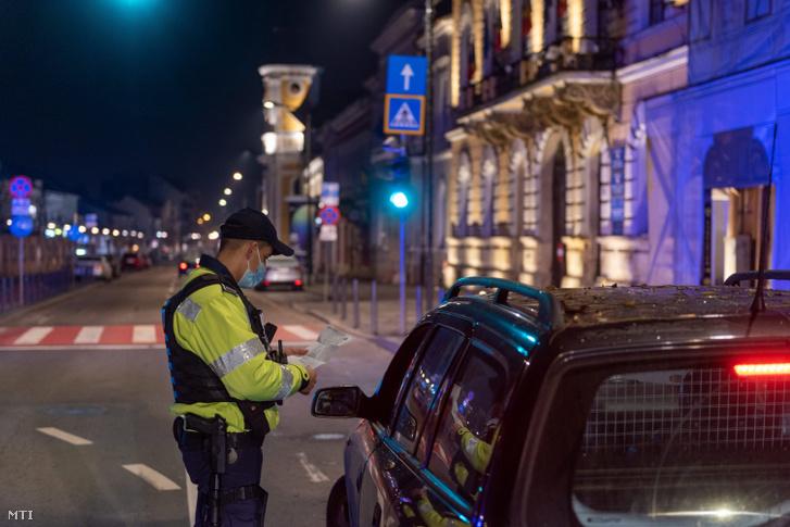 Rendőrök egy autó utasait ellenőrzik Kolozsvár központjában 2020. november 22-én éjjel
