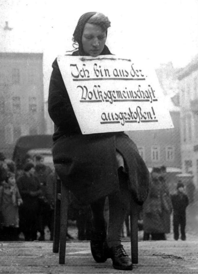 """Egy német nőnek így kellett kiállnia a főtérre 1942-ben, miután kitudódott, hogy egy lengyel férfival volt viszonya. A táblán ez áll: """"Ki vagyok zárva a nemzeti közösségből."""""""