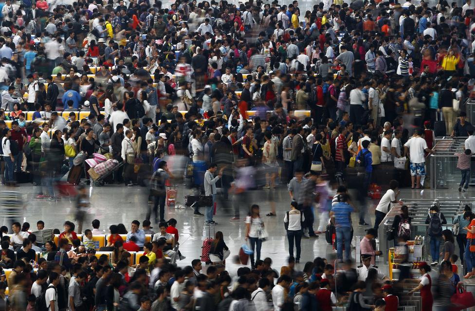 Ingázók egy hongkongi pályaudvaron egy nemzeti ünnep előtt.  Nyolcszázmillió vidékiként regisztrált kínai a városokba költözve sem jut a városiakkal megegyező szociális ellátáshoz, és minden hivatalos ügyben haza kell mennie egy 1958-ig visszanyúló szabályozás miatt, amit jócskán túlhaladott a kora.
