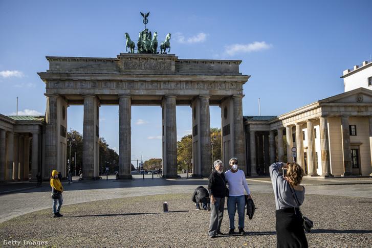 Néhány turista védőmaszkot viselve pózol a Brandenburgi kapu előtt Berlinben, Németországban 2020. november 3-án