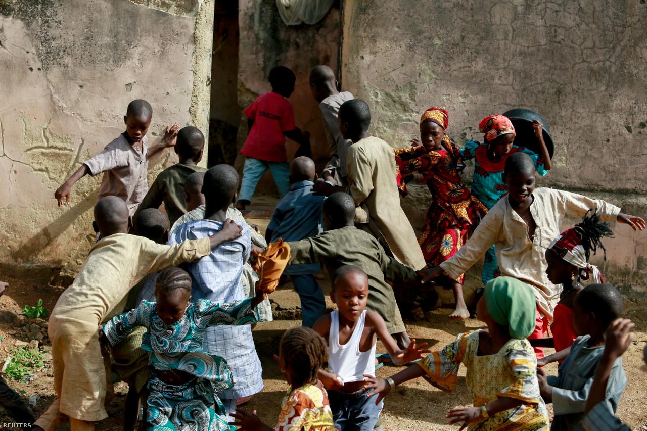 Fiatal gyerekek röppennek szét, miután a kép közepén látható piros pólós fiú megijeszti őket Kawu otthona mellett egy kígyóval.
