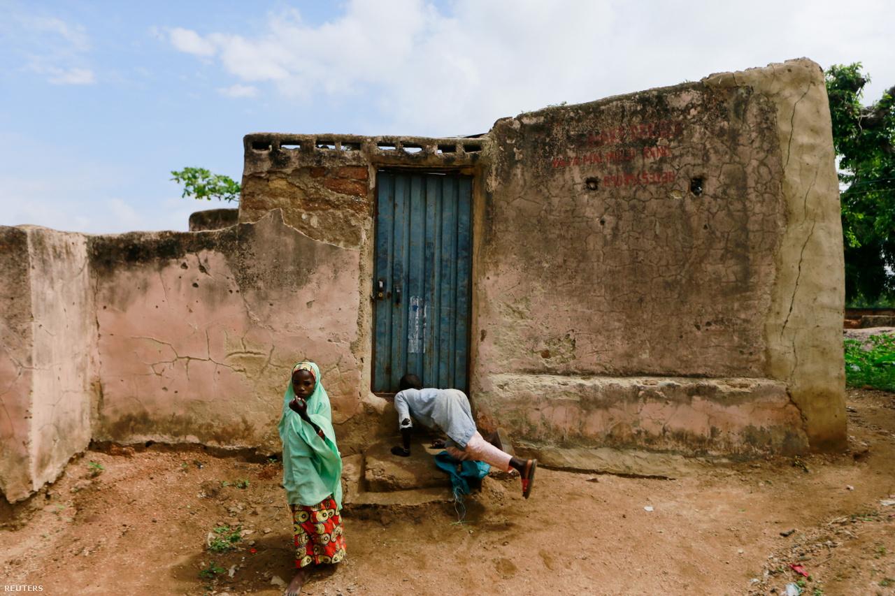 Fiatal fiú próbál belesni Kawu házának ajtaja alatt.