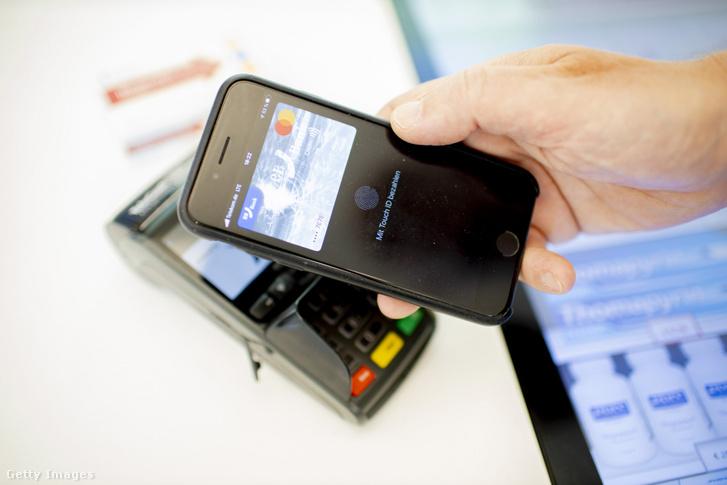 Érintésazonosítóval fizet mobiltelefonjával egy vásárló