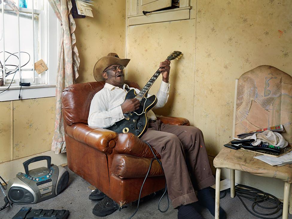 Glemie, a bluesgitáros, Westside, Detroit, 2011 Glemie, a remek bluesénekes valójában nyugdíjas kamionsofőr, ötven éve él Detroitban. A zenélésen kívül még kisvadakra vadászik, minden ősszel átlag 150 mosómedvét ejt el. A zsákmányt lenyúzza, kitömi, a húst pedig széles ügyfélkörének értékesíti, kiegészítve vele szerény nyugdíját. Egy, a rabszolgaság után béresként tengődő arkansas-i család szülöttjeként gyerekkorában gyakran napi 45 kiló gyapotot kellett szednie. A mosómedve a családi konyha specialitása volt.