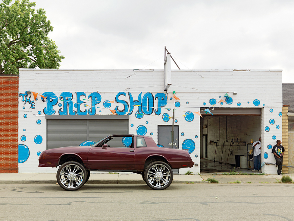 """Egy 28 colos kerekekkel pimpelt Chevy Monte Carlo a Conant Streeten, Northeast Side, Detroit, 2012 A Chevy Monte Carlo a detroiti autógyártás egyik ikonja. """"Újragondolva, újratervezve, újrahasznosítva, kultúrálisan újjászületve"""" - írja a lefotózott példányról Jordano. A műfajnak külön neve is van: Donk. A donkok a hetvenes-nyolcvanas években gyártott amerikai kocsik megemelt változatai, a középosztálybeli feketék gazdagságának szimbólumai. Az első donkok a déli államokban készültek, de már a detroiti kultúra részei. A Belle Isle Parkban gyakori a Donktalálkozó."""